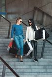 Beautiful girls with paper bags outside shopping mall. Young beautiful girls in sunglasses with paper bags walking on stairs out of shopping mall. Building on a royalty free stock images