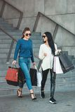 Beautiful girls with paper bags outside shopping mall. Young beautiful girls in sunglasses with paper bags walking on stairs out of shopping mall. Building on a royalty free stock photos