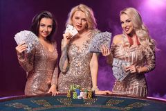 Beautiful girls with a perfect hairstyles and bright make-up are posing standing at a gambling table. Casino, poker. royalty free stock photo