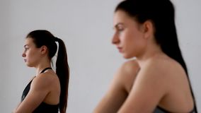 Beautiful girls perform an exercise for posture sitting in a butterfly posture. Pilates. yoga. The focus changes from. One person to another. Close-up. Portrait stock footage