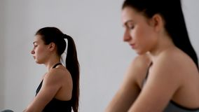 Beautiful girls perform an exercise for posture sitting in a butterfly posture. Pilates. yoga. The focus changes from. One person to another. Close-up. Portrait stock video