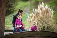 Beautiful girls in pink jackets and colorful skirts with mother on the bridge. Mother having fun with identical twins on bridge, blond cute girls with mother Royalty Free Stock Photo