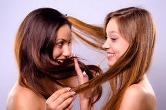 Beautiful girls playing with their hair Stock Images