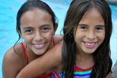 Beautiful girls in the pool. Two beautiful Hispanic sisters smiling in a pool Royalty Free Stock Photo