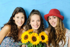 Beautiful girls. Portrait of beautiful girls with sunflowers on blue background Stock Images