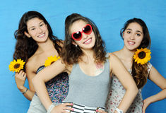 Beautiful girls. Portrait of beautiful girls with sunflowers on blue background Stock Photography