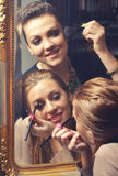Beautiful girls putting make up in front of the old mirror Stock Photos