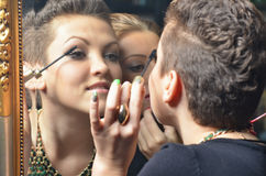 Beautiful girls putting make up in front of old mirror Stock Photo