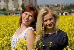 Beautiful girls on rapeseed field Royalty Free Stock Image
