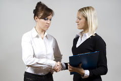 Beautiful girls shaking hands on. Beautiful girls shaking hands after signing the contract Stock Image