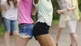 Beautiful girls shaking bodies, dancing to music at outdoor summer party