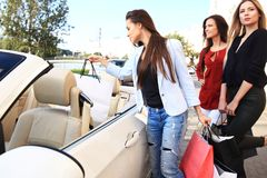 Beautiful girls with shopping bags are discussing purchases and smiling while leaning on their car Royalty Free Stock Image
