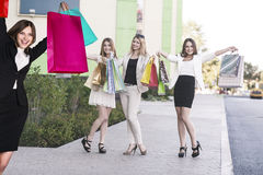 Beautiful girls with shopping bags near mall. Beautiful girls with shopping bags in ctiy near mall. Shopping and tourism concept Royalty Free Stock Image