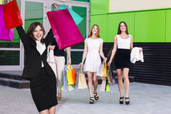 Beautiful girls with shopping bags near mall. Beautiful girls with shopping bags in ctiy near mall. Shopping and tourism concept Royalty Free Stock Photo