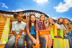 Beautiful girls with shopping bags sit on bench. Beautiful girls with shopping bags sitting together on wooden bench and smile happily on urban background in Royalty Free Stock Image