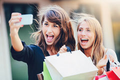 Beautiful girls with shopping bags taking a Royalty Free Stock Images