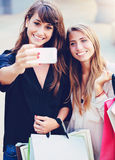 Beautiful girls with shopping bags taking a royalty free stock photography