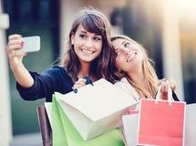 Beautiful girls with shopping bags taking a Stock Image