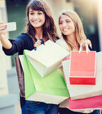 Beautiful girls with shopping bags taking a Royalty Free Stock Photo
