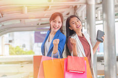 Beautiful girls with shopping bags walking at the mall Stock Photos