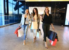 Beautiful girls with shopping bags walking at the mall. Stock Images
