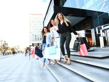 Beautiful girls with shopping bags walking at the mall. Stock Image