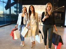 Beautiful girls with shopping bags walking at the mall. Royalty Free Stock Photo