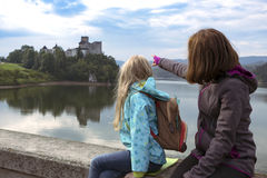 Beautiful girls sit and look at the castle niedzica Stock Images