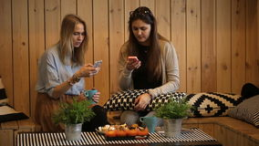 Beautiful girls sitting in cafe with tea and looking at smart phone. stock footage