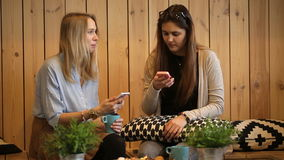 Beautiful girls sitting in cafe with tea and looking at smart phone. stock video