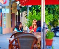 Beautiful girls sitting on cafe terrace, summer. City royalty free stock photo