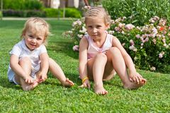 Beautiful girls sitting on the green grass Royalty Free Stock Image