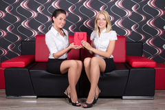 Beautiful girls sitting on the sofa with present Royalty Free Stock Photos