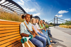 Beautiful girls sitting on wooden bench in a row Royalty Free Stock Photo