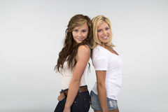 2 Beautiful girls smiling against a white background Royalty Free Stock Photo