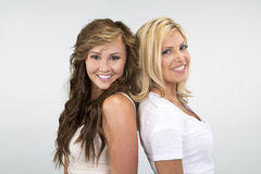 2 Beautiful girls smiling against a white background Royalty Free Stock Photos