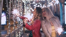 Beautiful girls with sparkling fireworks celebrate a holiday in the night city and have fun. SLOW MOTION stock video footage