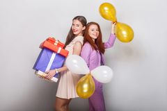 Beautiful girls standing back to back, holding many box and air Royalty Free Stock Photo