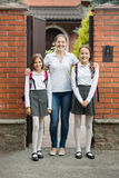 Beautiful girls standing with their mother in doorway before goi Royalty Free Stock Image