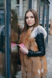 Beautiful girls on the street. Young model walk around town in fur coatsr Stock Photography
