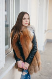 Beautiful girls on the street. Young model walk around town in fur coatsr royalty free stock image