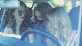 Beautiful girls are studying a map and smiling while traveling by car stock footage
