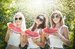 Beautiful girls with sunglasses eating fresh watermelon laughing. Happy young women holding watermelon slices outdoors Stock Image