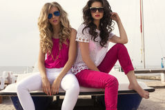 Beautiful girls with sunglasses posing on summer beach Stock Photos