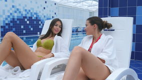 Beautiful girls in swimwear and bathrobes talking and smiling while relaxing on chaise longues near the pool. Professional shot on Lumix GH4 in 4K resolution stock video