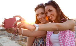 Beautiful girls taking a selfie on the roof at sunset. Royalty Free Stock Photography