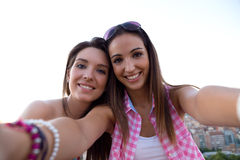 Beautiful girls taking a selfie on the roof at sunset. Royalty Free Stock Photo