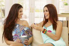 Beautiful girls talking at home on sofa Stock Photo