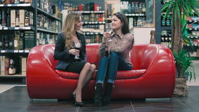Beautiful girls are talking on the sofa in the shop. Beautiful blonde and brunette sitting on the sofa in the shop. They holding a glasses with red and white stock footage