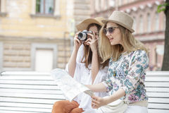 Beautiful girls tourists are looking for an address on the map sitting on the bench. They are wearing hats and smiling. Outdoors Stock Photo